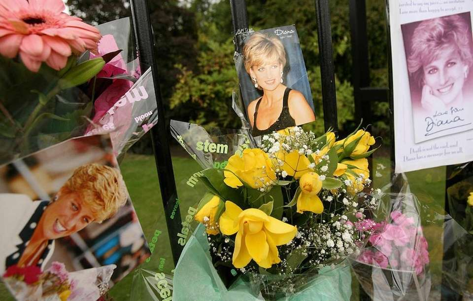 Well-wishers leave flowers and messages outside the gates