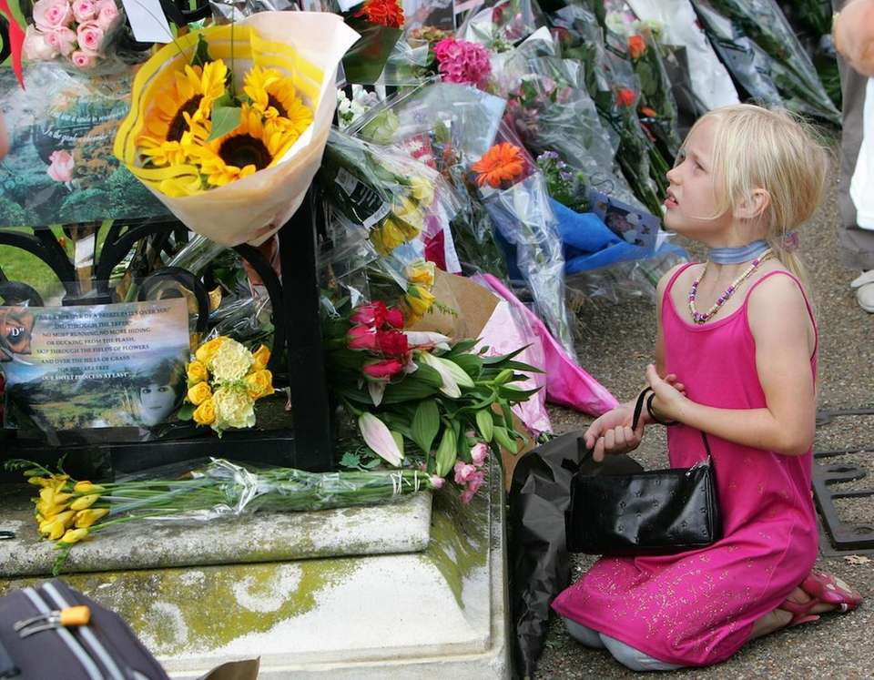 A girl looks at floral tributes outside the
