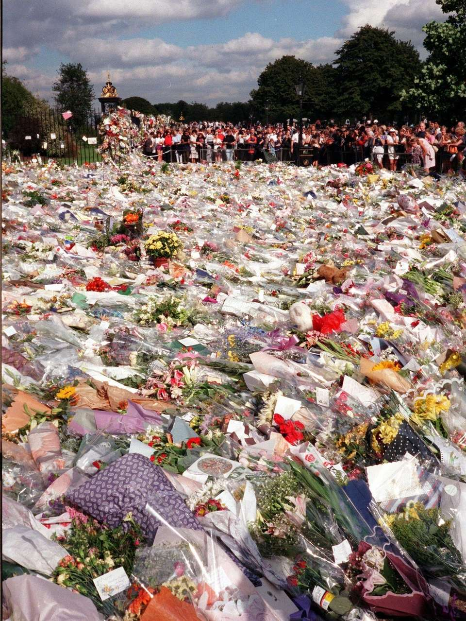 Mourners stand by a sea of flowers outside
