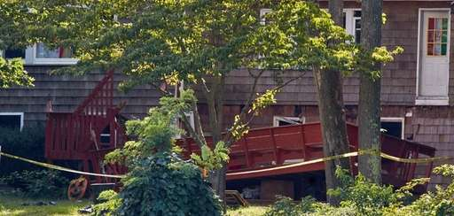 Police tape surrounds a deck that collapsed during