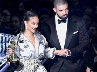 Rihanna is escorted by Drake after he presented