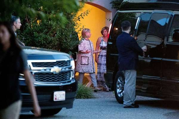 Hillary Clinton, center left, leaves the home of