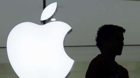 A person stands near the Apple logo at