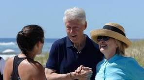 Hillary and Bill Clinton walk along the ocean