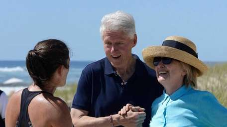 Hillary and Bill Clinton walk along the ocean