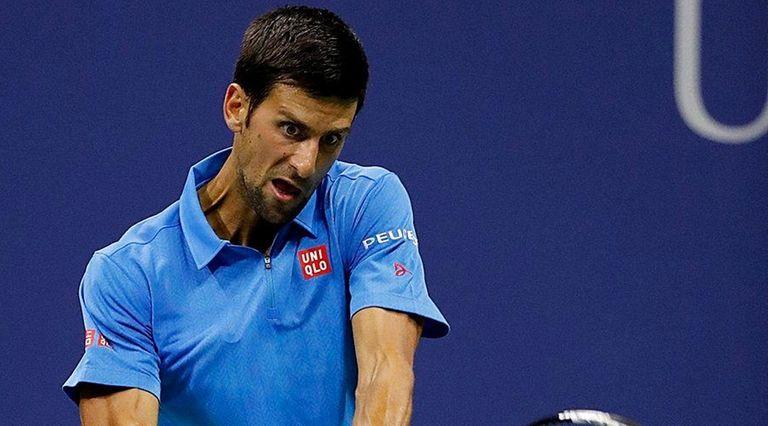 Novak Djokovic hits the backhand return against Jerzy