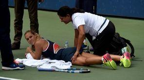 Dominika Cibulkova of Slovakia gets medical attention on