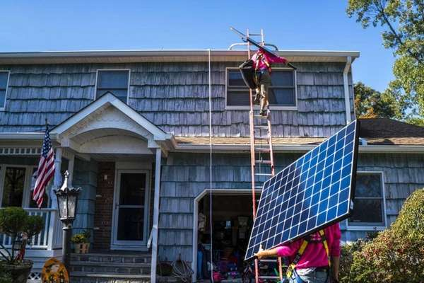 Employees of SunNation install solar panels at a
