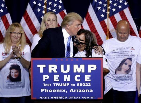 Republican presidential candidate Donald Trump hugs a woman,