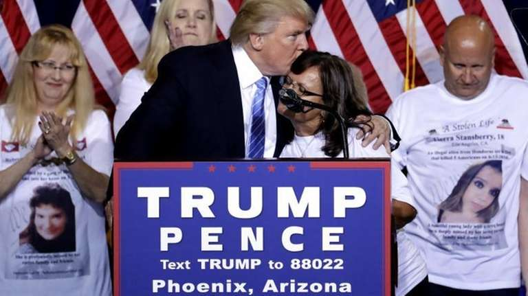 Republican presidential candidate Donald Trump hugs a woman,