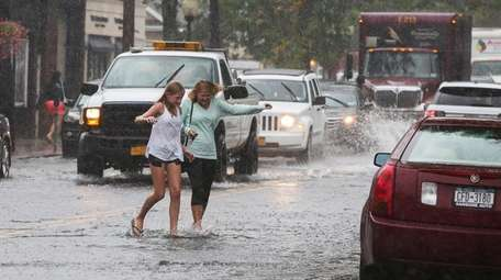 Two women cross a flooded section of Main