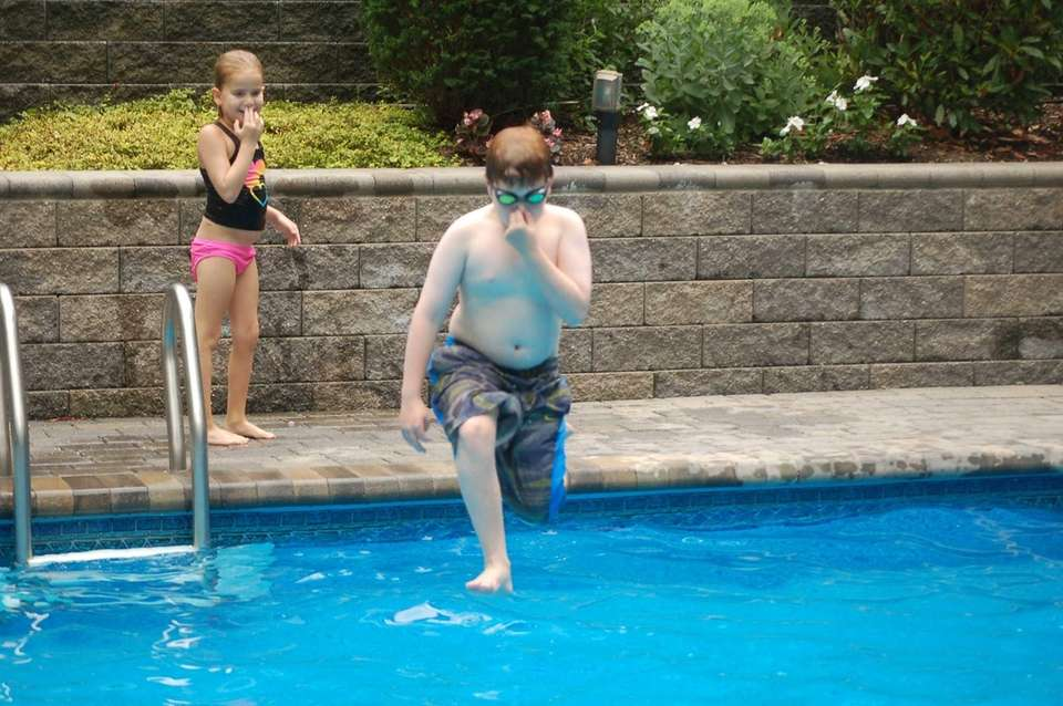 Zachary jumping into pool as cousin Ella looks