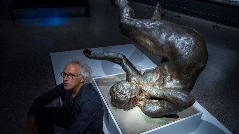 Artist Eric Fischl sits next to his sculpture