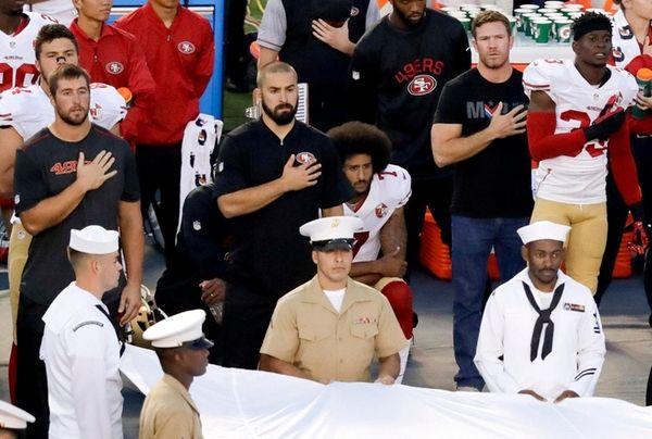 San Francisco 49ers quarterback Colin Kaepernick, middle, sits