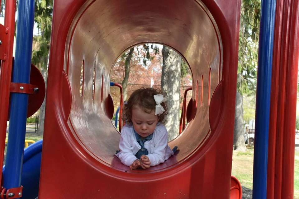 Lily laying in a slide at the park