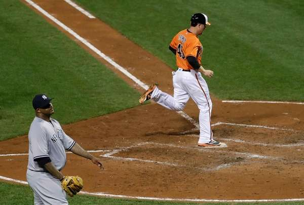 Baltimore Orioles' Mark Trumbo, right, jogs past New
