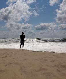 A beachgoer stands at the edge of the
