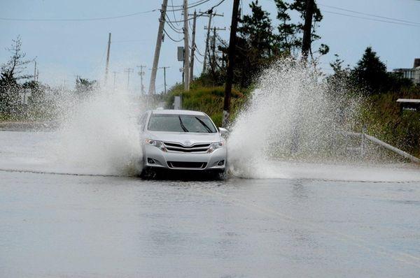 A car makes a splash on a flooded