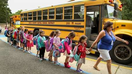 A staffer leads kindergartners into the Unity Drive