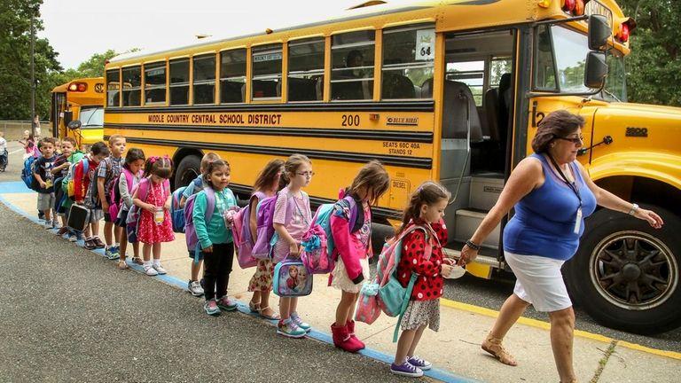 A staffer leads kindergartners into the Unity Drive