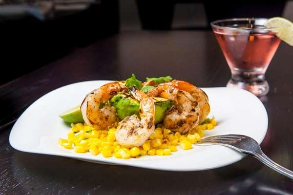 Avocado buoys grilled shrimp on a bed of