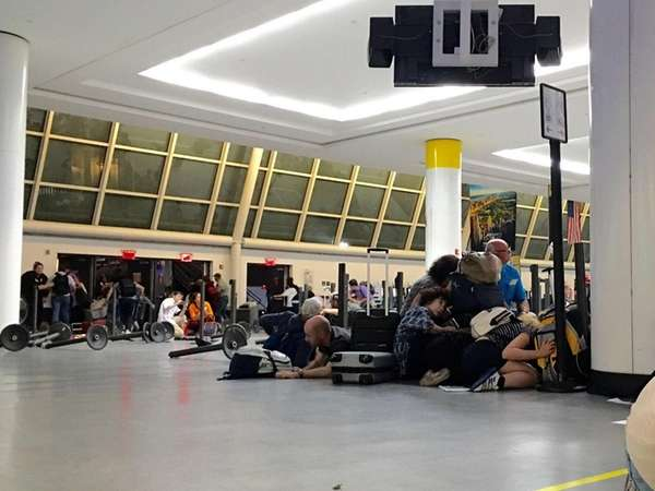 Passengers hunker down at immigration control while police