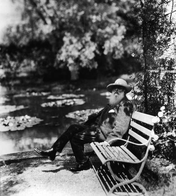 Monet sits on a bench beside the water