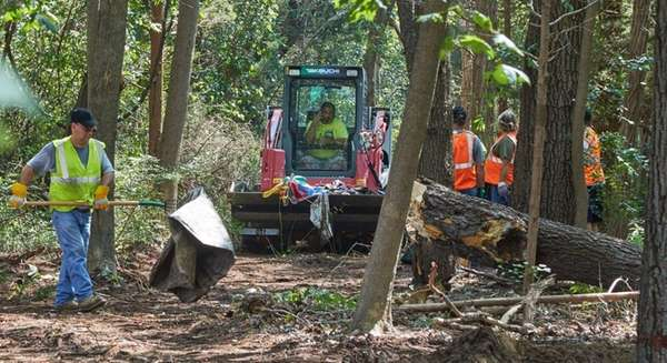 Workers remove debris from a homeless camp along