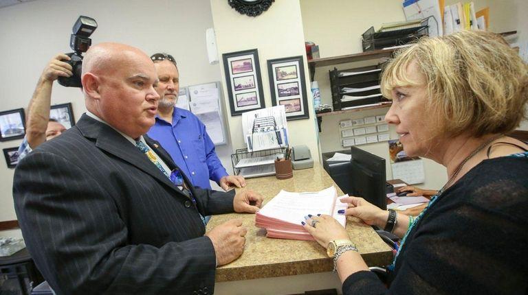 Bob Miller, left, turns over stacks of signatures