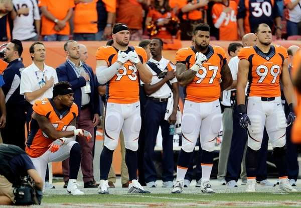 Broncos linebacker Brandon Marshall kneels during the national