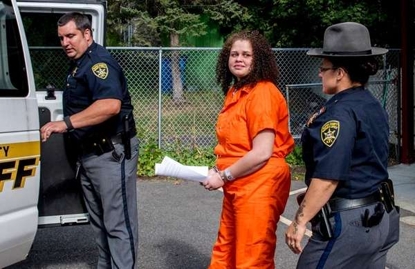 Sarra Gilbert is escorted to a waiting sheriff's