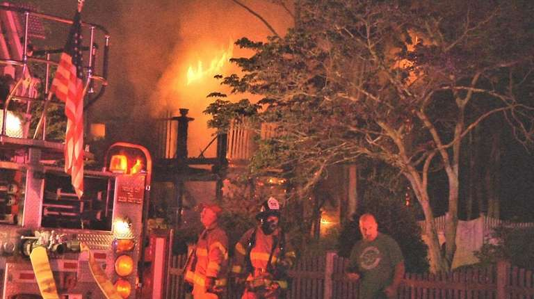 Firefighters fight a blaze that engulfed a house