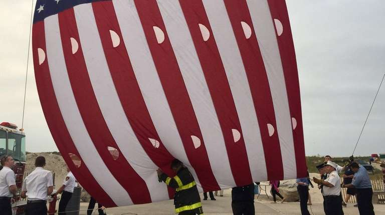 Firefighters unfurl an American flag during a 9/11