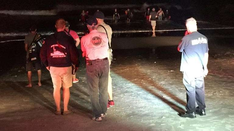Emergency personnel search for missing swimmer who was