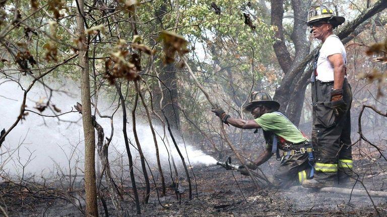 Firefighters battle a brush fire in the Hempstead