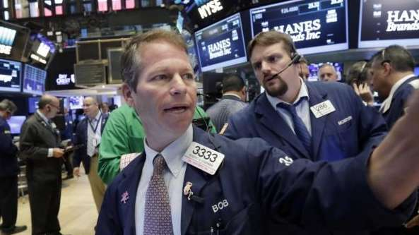 Trader Robert Charmak, foreground, works on the floor