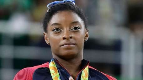 American gold medalist Simone Biles stands for the