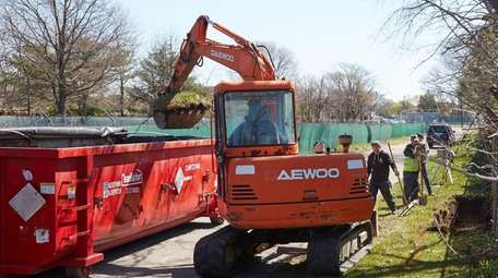 Workers remove contaminated soil suspected of containing polychlorinated