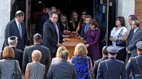 The casket is brought out of Guttermans Funeral