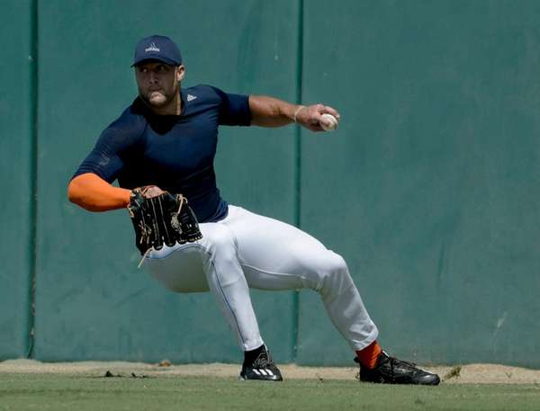 Tim Tebow fields a ball for baseball scouts