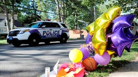 A police vehicle drives by a makeshift memorial