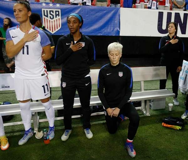 USA's Megan Rapinoe, right, kneels next to teammates