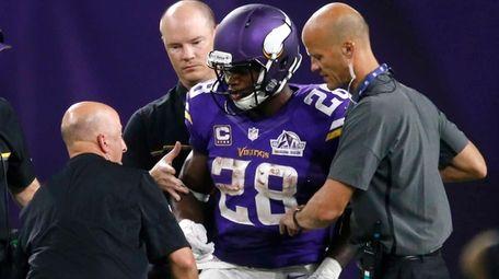 Minnesota Vikings running back Adrian Peterson is helped