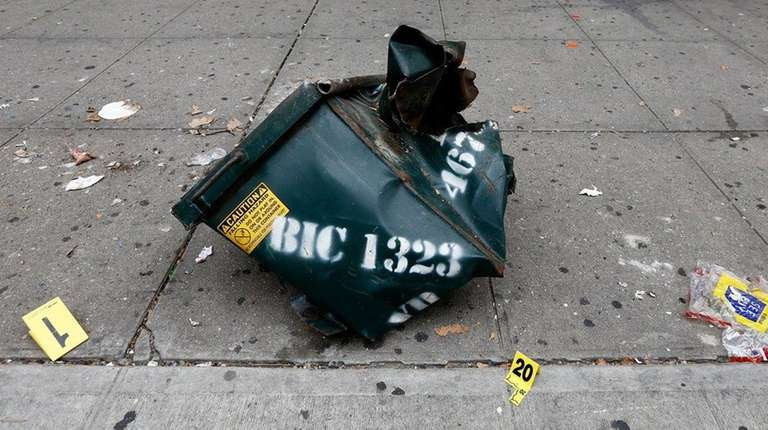 A mangled dumpster sits on the sidewalk at