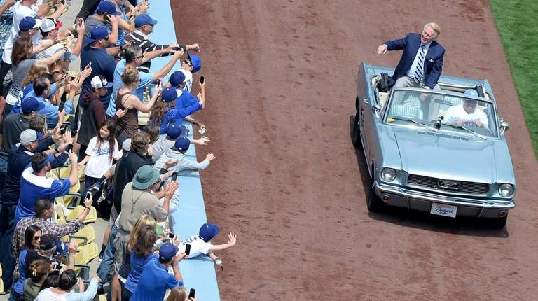 Vin Scully waves to fans from a car