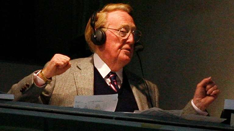 Vin Scully broadcasts from a booth at Dodger