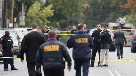 Law enforcement officials gather at the site where