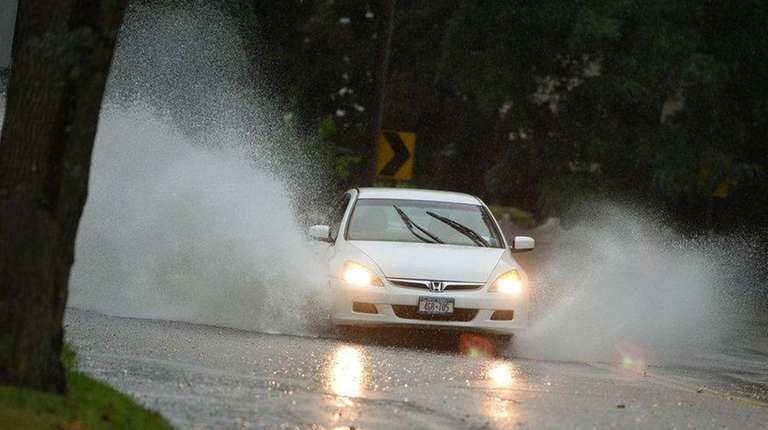 Cars drive through floodwater on Laurel Road in