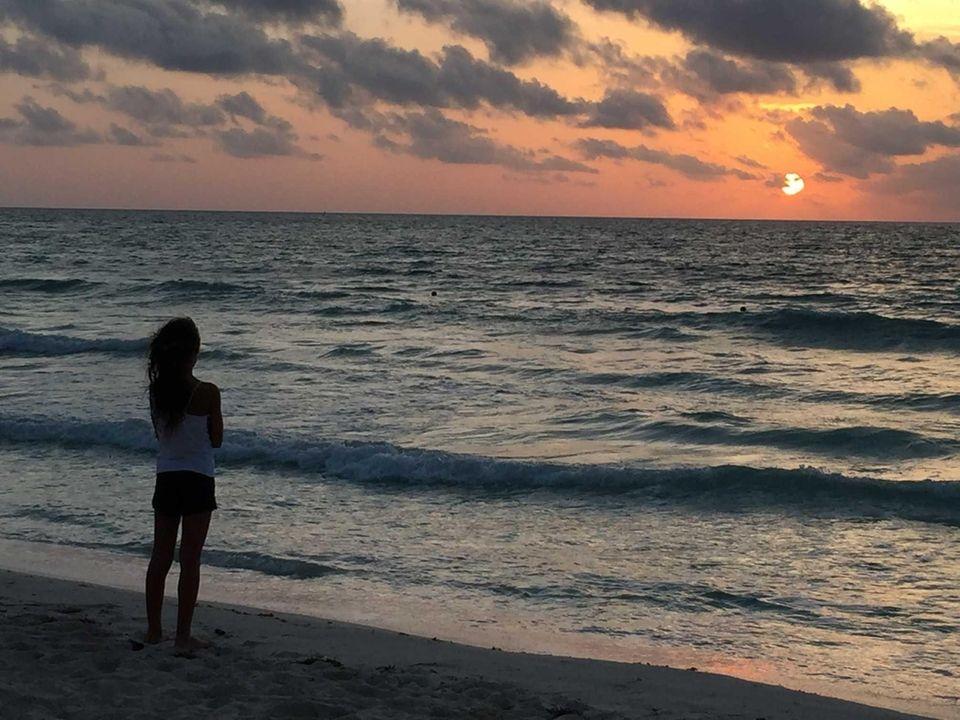 My daughter watching the sunrise in Riveria Maya,