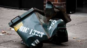 A mangled dumpster sits on the sidewalk on